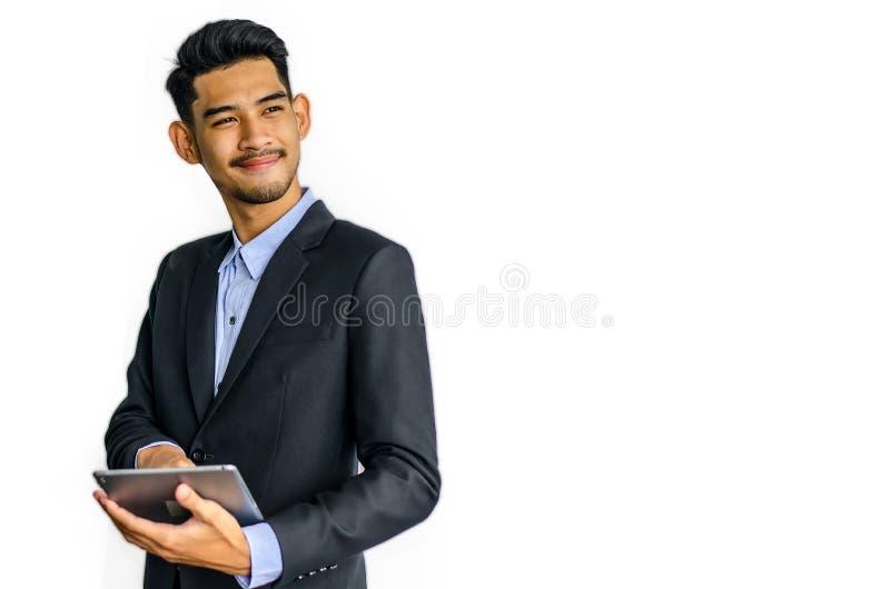 Giovane uomo d'affari asiatico bello con la compressa che comunica immagini stock