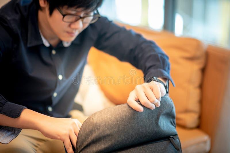 Giovane uomo d'affari asiatico che apre la sua borsa in salone immagine stock libera da diritti