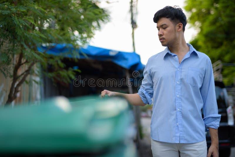 Giovane uomo d'affari asiatico che controlla l'immondizia nel outd delle vie fotografia stock