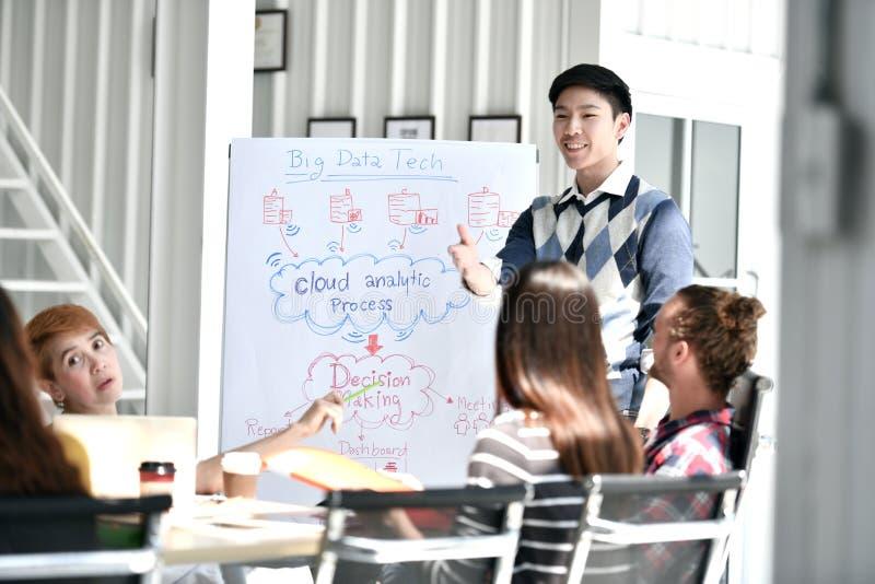 Giovane uomo d'affari asiatico che dà presentazione sui progetti per il futuro ai suoi colleghi fotografia stock