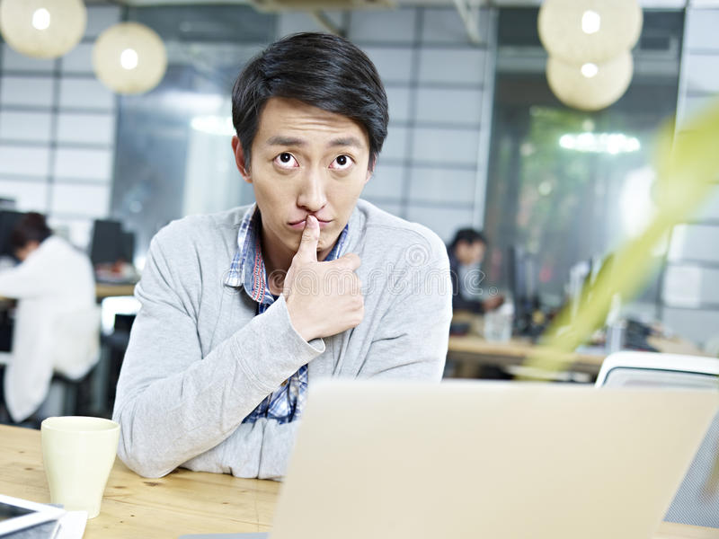 Giovane uomo d'affari asiatico che pensa duro nell'ufficio fotografia stock libera da diritti