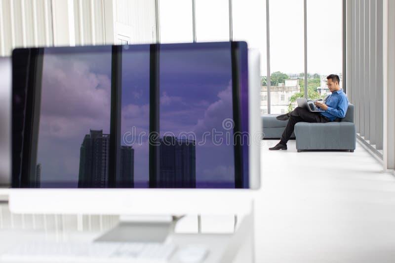 Giovane uomo d'affari asiatico che si siede sul sofà con il computer portatile e immagini stock libere da diritti