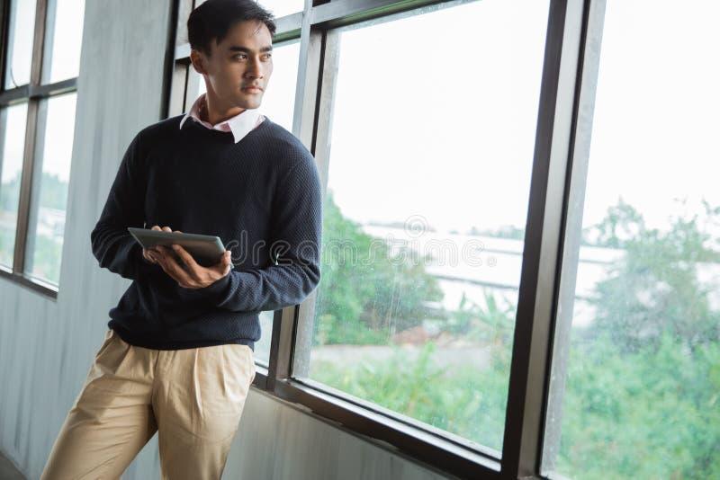 Giovane uomo d'affari asiatico con uno sguardo di condizione del cuscinetto fuori per le finestre fotografia stock libera da diritti
