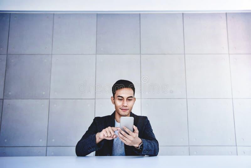 Giovane uomo d'affari asiatico felice Working su Smartphone Sorridendo e sedersi allo scrittorio nell'ufficio industriale del sot fotografie stock libere da diritti