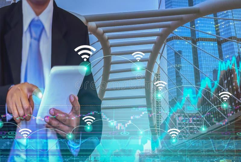 Giovane uomo d'affari asiatico, indossante un vestito, collegamento a Internet senza fili sullo schermo della compressa immagine stock libera da diritti