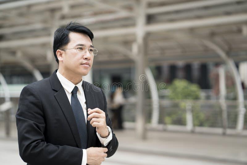Giovane uomo d'affari asiatico sicuro nella città diritta del vestito immagine stock