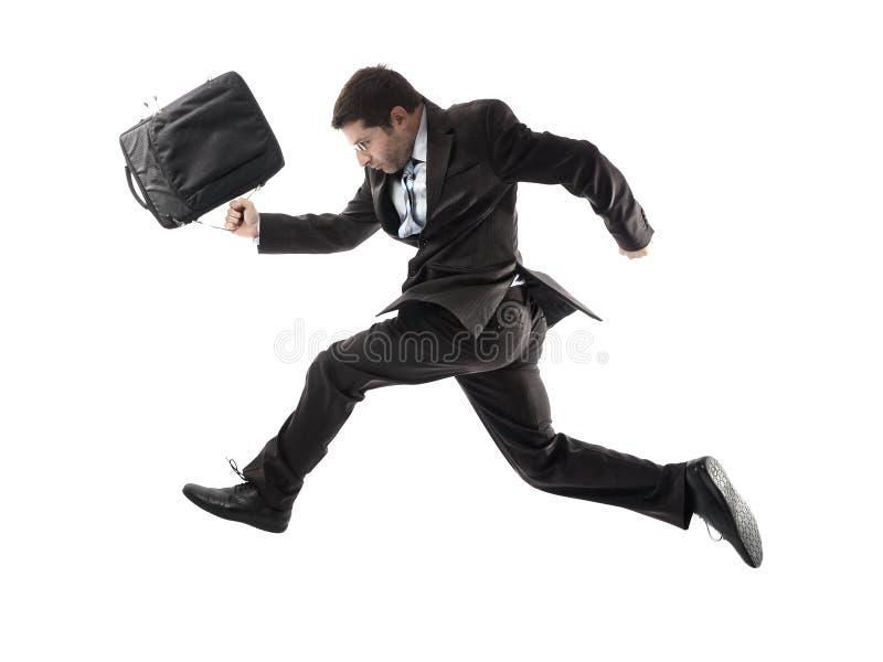 Giovane uomo d'affari attraente che corre tardi per lavorare nello sforzo immagine stock