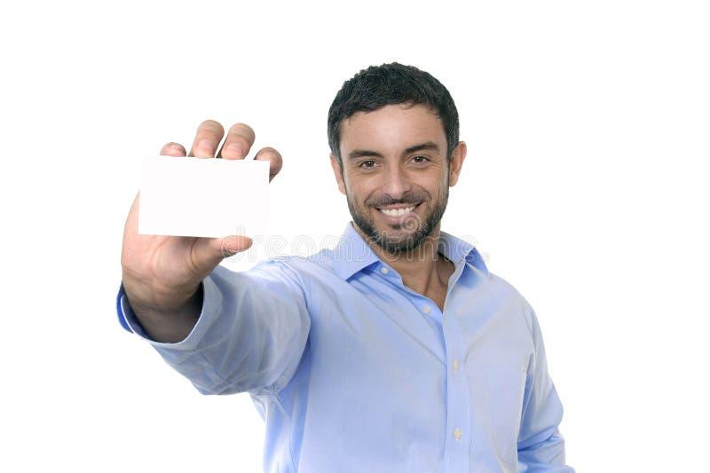 Giovane uomo d'affari attraente felice che tiene biglietto da visita in bianco con lo spazio della copia fotografia stock