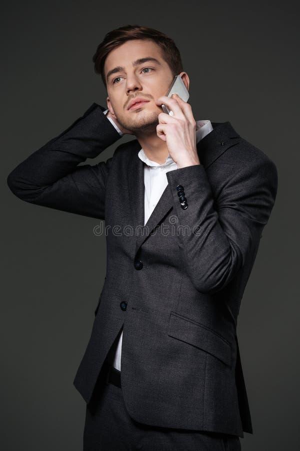 Giovane uomo d'affari attraente pensieroso in vestito nero che parla sullo smartphone fotografie stock libere da diritti