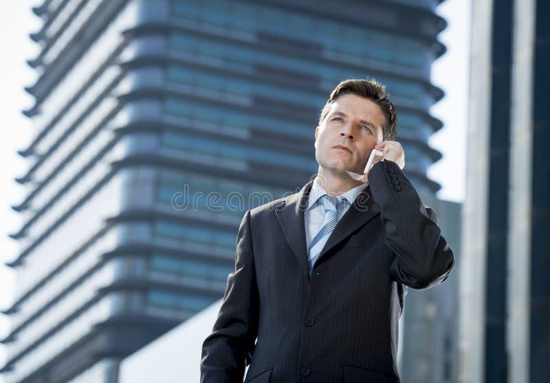 Giovane uomo d'affari attraente in vestito e legame che parlano sul telefono cellulare all'aperto immagini stock