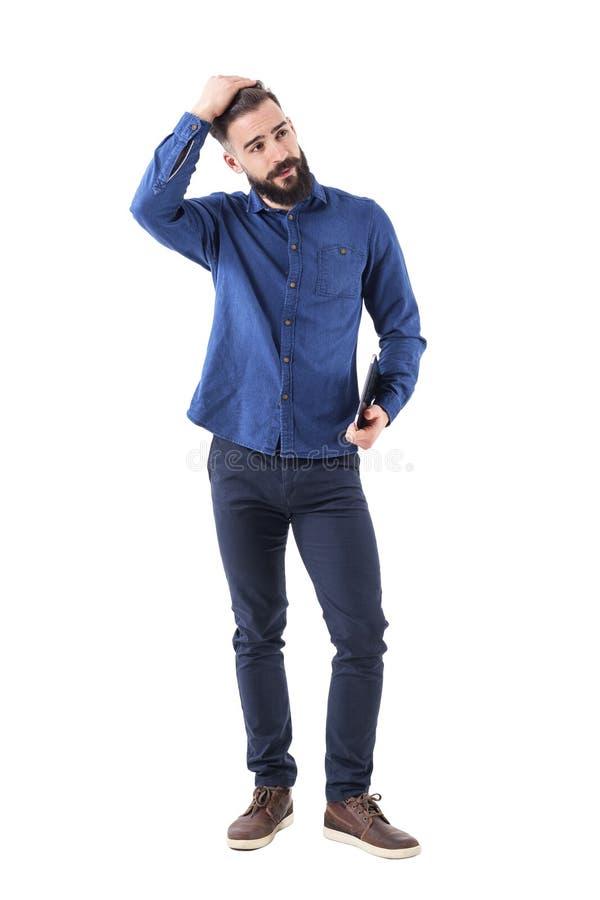 Giovane uomo d'affari barbuto bello che regola capelli con la mano nella compressa e nel distogliere lo sguardo della tenuta dei  fotografia stock libera da diritti