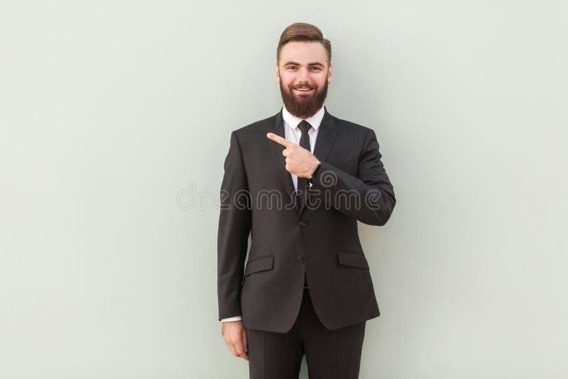 Giovane uomo d'affari barbuto bello con il sorriso di orientamento che indica w immagine stock libera da diritti