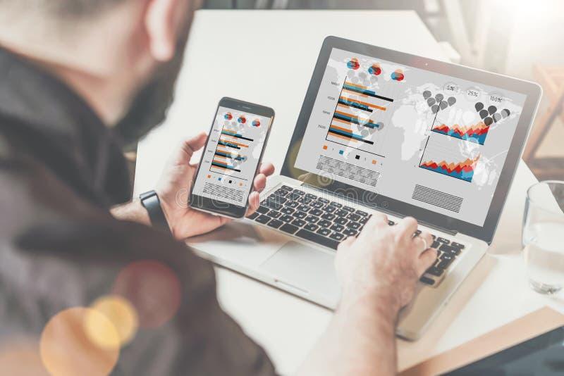 Giovane uomo d'affari barbuto in camicia che si siede allo scrittorio e che per mezzo del computer portatile mentre tenendo smart immagine stock