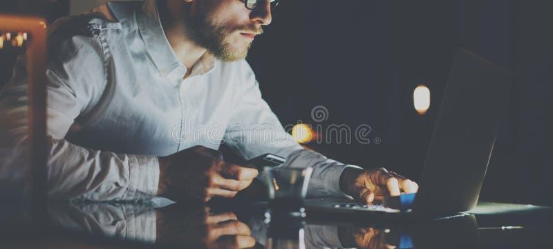 Giovane uomo d'affari barbuto che lavora all'ufficio alla notte Uomo che per mezzo del taccuino contemporaneo per il messaggio ma immagine stock libera da diritti