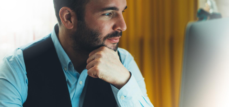 Giovane uomo d'affari barbuto che lavora all'ufficio moderno alla notte Sguardo di pensiero dell'uomo del consulente in computer  fotografia stock