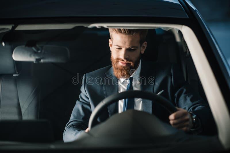 Giovane uomo d'affari barbuto che si siede in nuova automobile fotografie stock