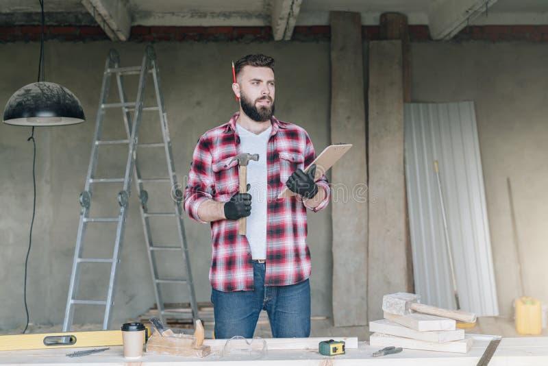 Giovane uomo d'affari barbuto, costruttore, riparatore, carpentiere, architetto, progettista, sugli strumenti della costruzione d immagine stock