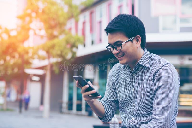 Giovane uomo d'affari bello asiatico che sorride mentre leggendo il suo astuto fotografie stock