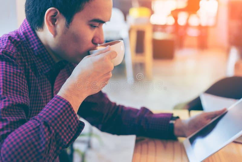 Giovane uomo d'affari bello asiatico che sorride mentre leggendo la sua tavola immagine stock
