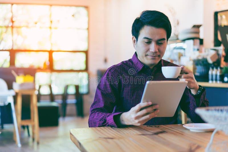 Giovane uomo d'affari bello asiatico che sorride mentre leggendo la sua tavola fotografia stock libera da diritti