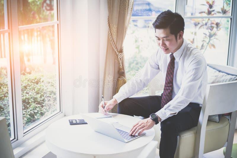 Giovane uomo d'affari bello asiatico felice facendo uso del computer portatile fotografie stock