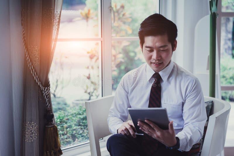 Giovane uomo d'affari bello asiatico felice facendo uso della compressa immagine stock libera da diritti
