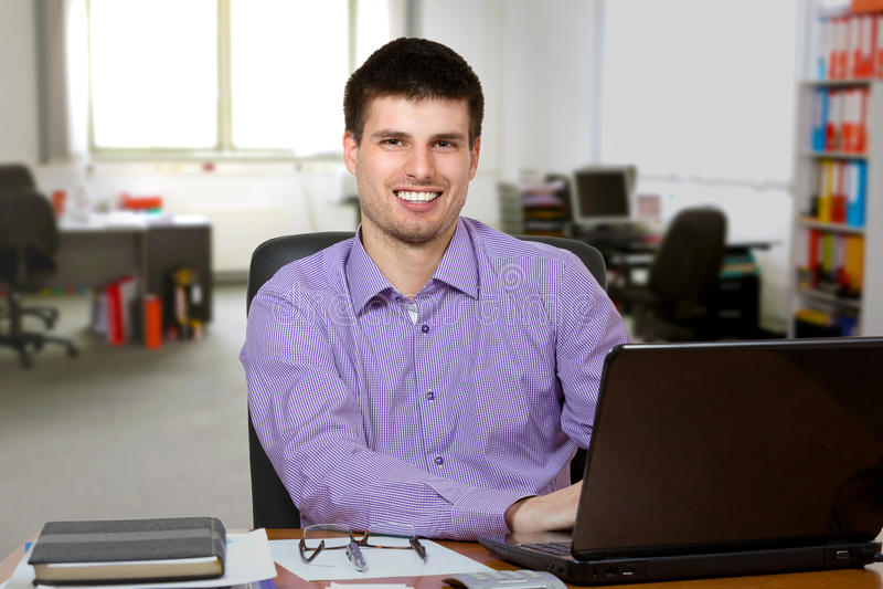 Giovane uomo d'affari bello che lavora al computer portatile immagine stock libera da diritti