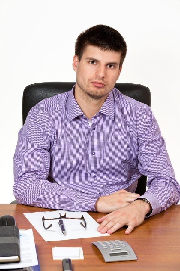 Giovane uomo d'affari bello che lavora al suo scrittorio fotografie stock