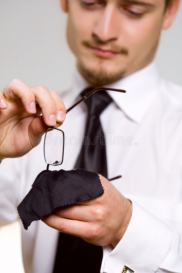 Giovane uomo d'affari bello che pulisce gli occhiali fotografia stock