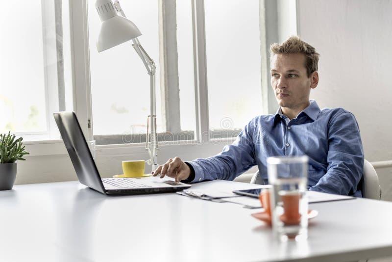 Giovane uomo d'affari bello che si siede al suo funzionamento della scrivania immagine stock