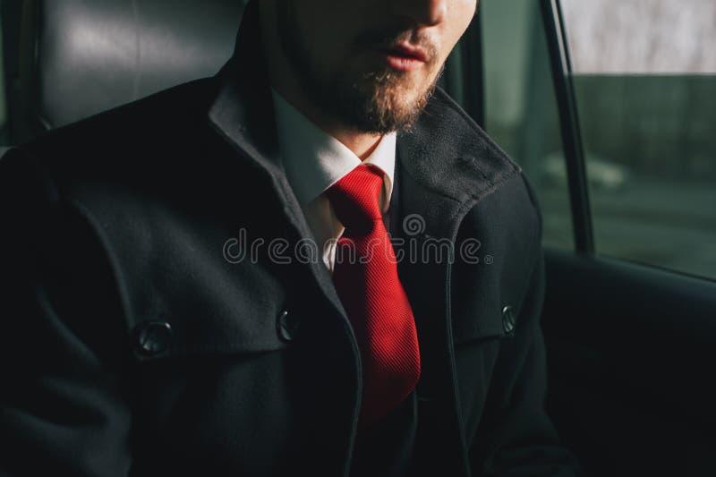 Giovane uomo d'affari bello che si siede nell'automobile fotografie stock