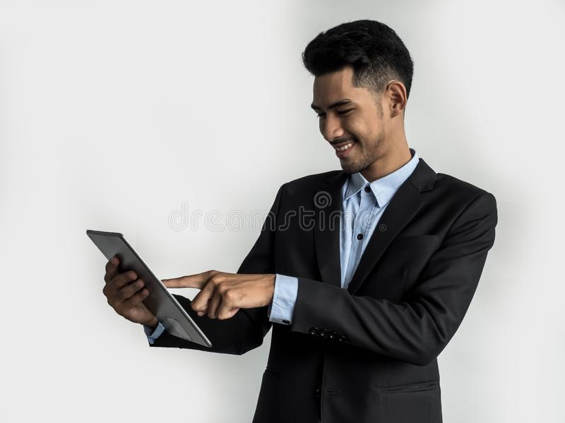 Giovane uomo d'affari bello con la compressa che comunica sul fondo bianco immagine stock
