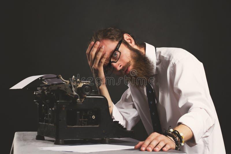 Giovane uomo d'affari bello dei pantaloni a vita bassa che pensa e che scrive con la macchina da scrivere d'annata immagine stock