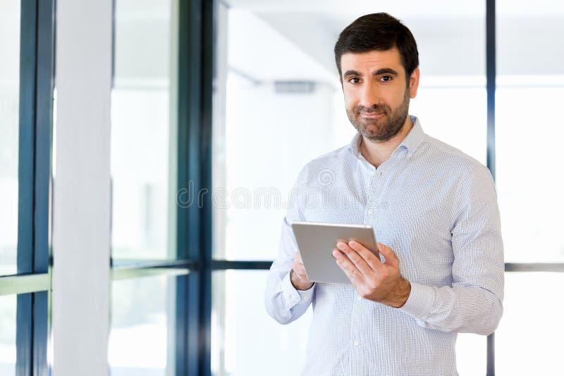 Giovane uomo d'affari bello facendo uso del suo touchpad che sta nell'ufficio immagini stock libere da diritti
