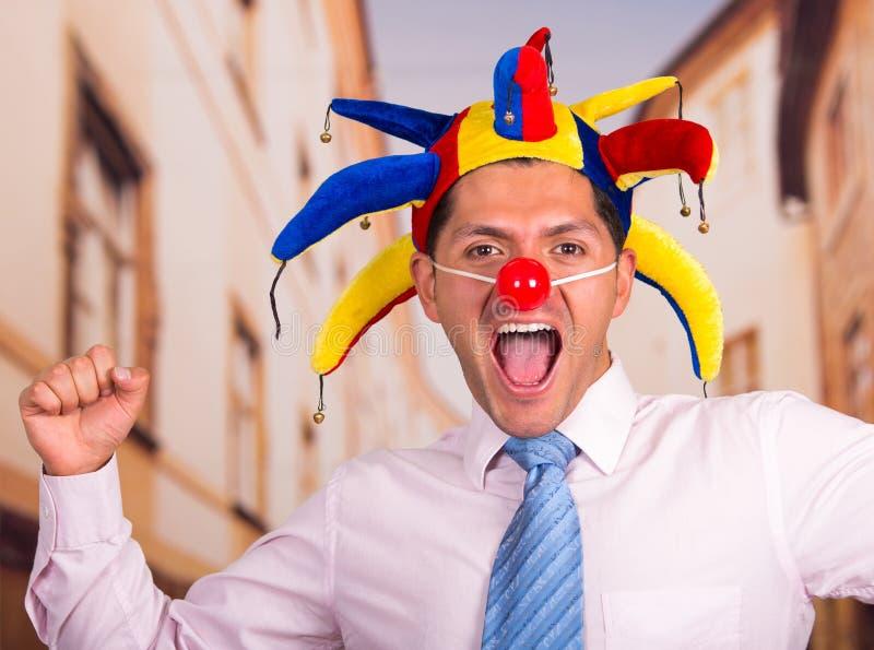 Giovane uomo d'affari bello felice con un naso rosso del pagliaccio e capanna variopinta dell'arlecchino in sua testa fotografia stock libera da diritti