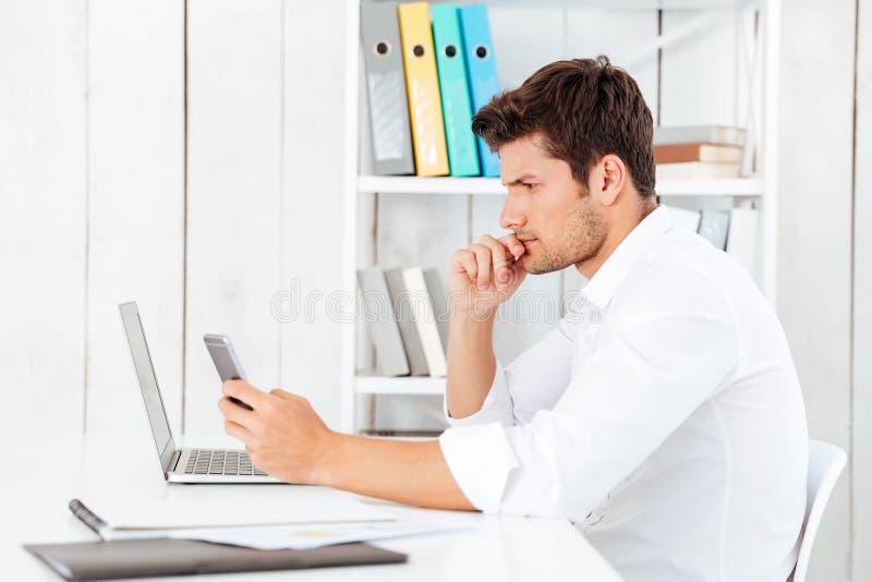 Giovane uomo d'affari in camicia bianca che funziona con il computer portatile e lo smartphone immagine stock libera da diritti
