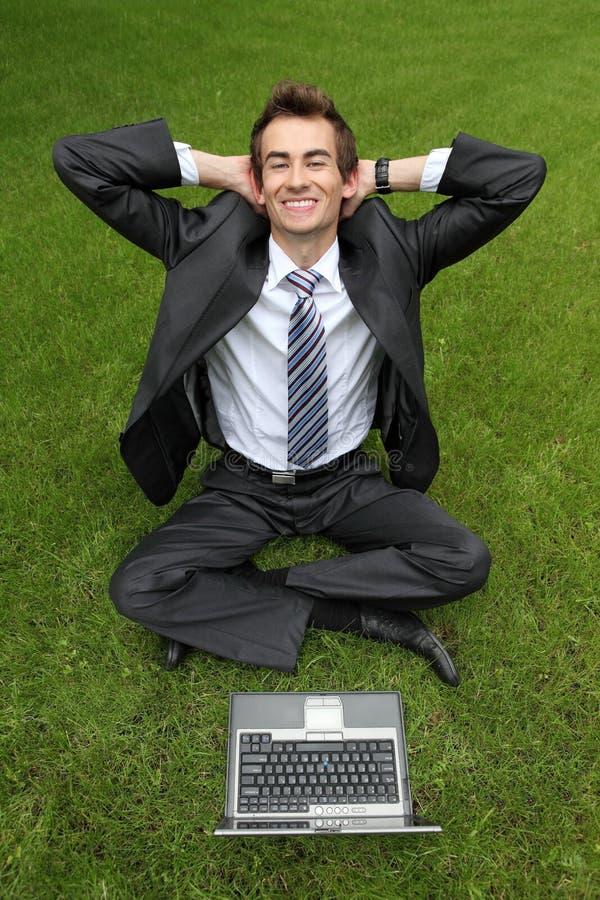 giovane uomo d'affari caucasico che si rilassa sull'erba con il suo computer portatile fotografie stock libere da diritti