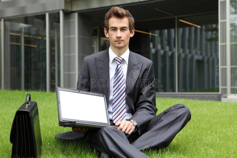 giovane uomo d'affari caucasico che si siede sull'erba facendo uso del suo computer portatile immagini stock