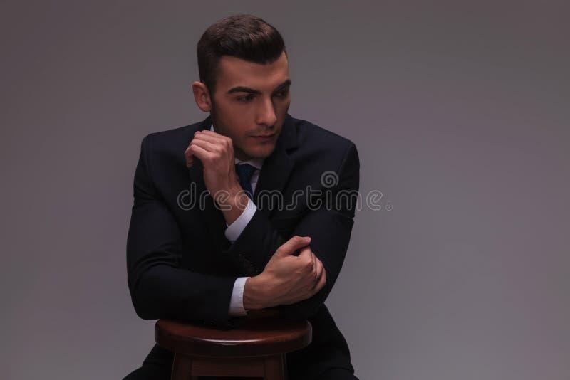 Giovane uomo d'affari che è alla moda con le mani su una sedia fotografia stock