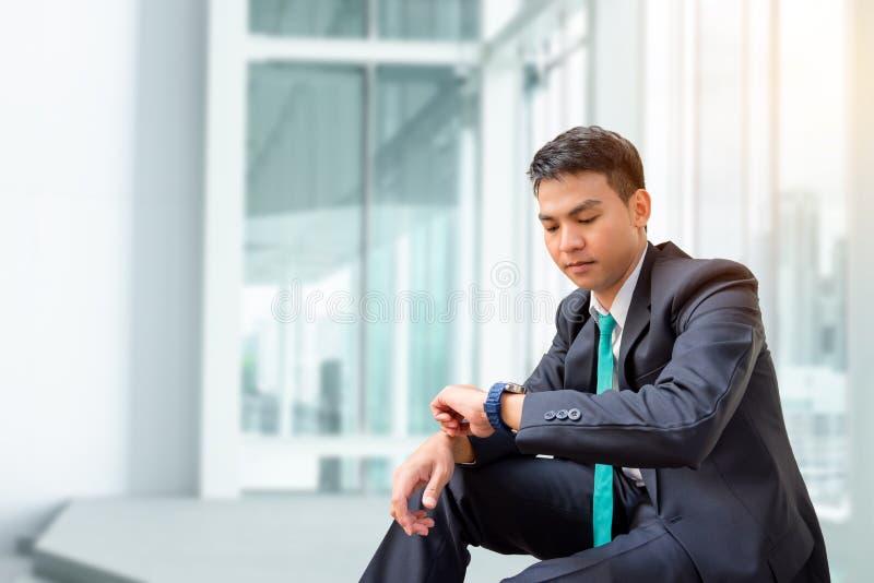 Giovane uomo d'affari che esamina orologio fotografia stock libera da diritti