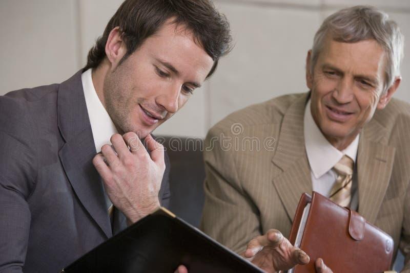 Giovane uomo d'affari che esamina un dispositivo di piegatura fotografie stock libere da diritti