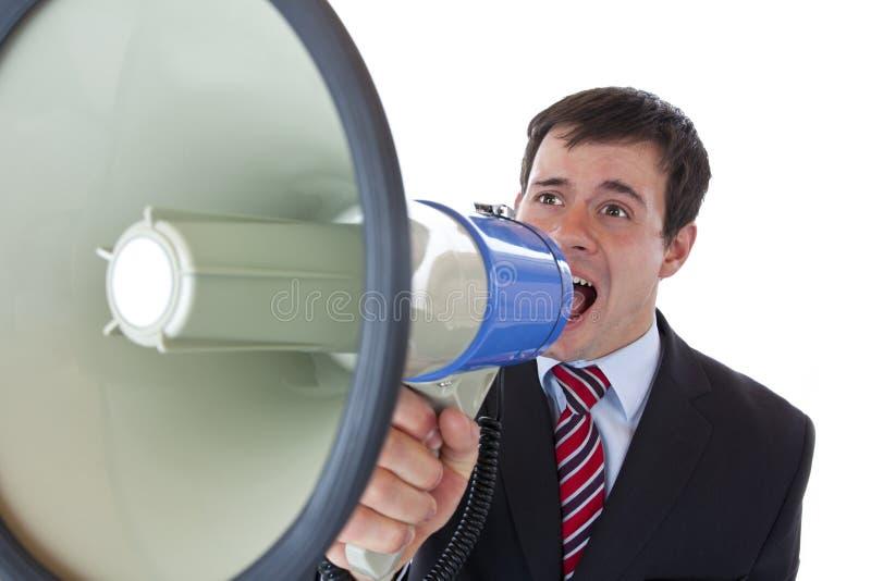 Giovane uomo d'affari che grida fortemente nel megafono fotografia stock