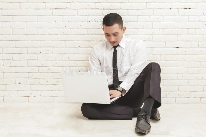 Giovane uomo d'affari che lavora al computer portatile mentre sedendosi sul pavimento fotografia stock libera da diritti