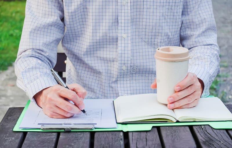 Giovane uomo d'affari che lavora al parco fuori sul banco di legno Testo di scrittura dell'uomo, vista della via fotografia stock libera da diritti
