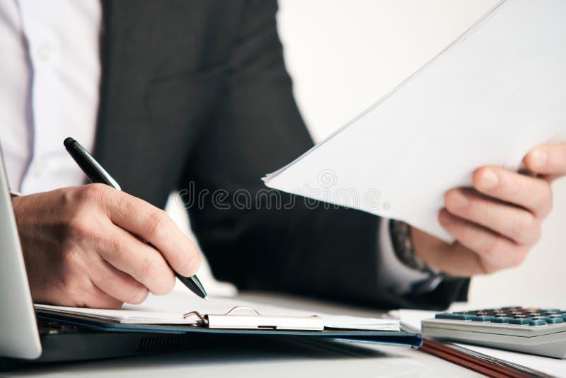 Giovane uomo d'affari che lavora al suo ufficio con i documenti immagini stock