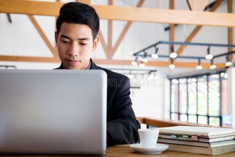 Giovane uomo d'affari che lavora con il computer portatile fotografia stock libera da diritti