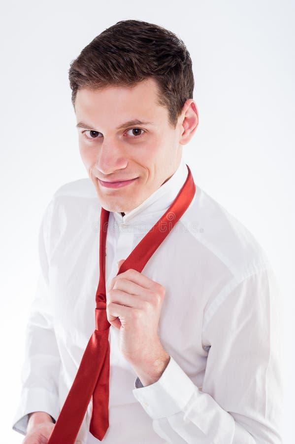 Giovane uomo d'affari che lega un legame rosso fotografia stock libera da diritti