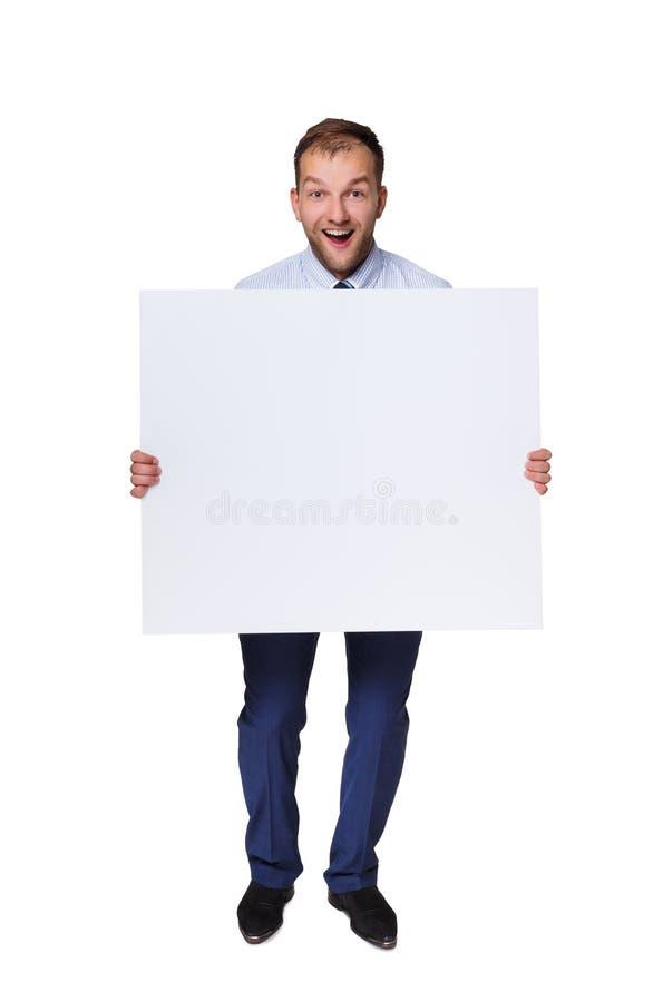 Giovane uomo d'affari che mostra insegna in bianco con lo spazio della copia isolato su fondo bianco fotografie stock