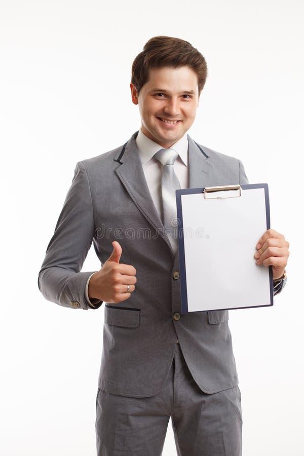 Giovane uomo d'affari che mostra lavagna per appunti in bianco, isolata su fondo bianco Successo nel colpo di concetto di affari, fotografia stock