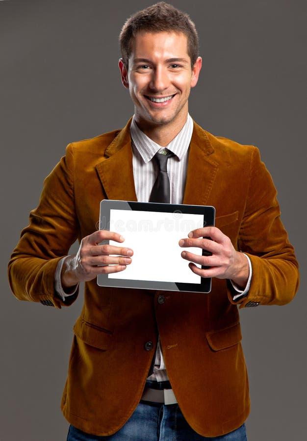 Giovane uomo d'affari che mostra uno schermo della compressa. fotografia stock